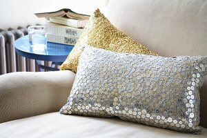Sequinned cushions on light armchair