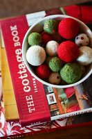 Felt Christmas tree baubles on a stack of books