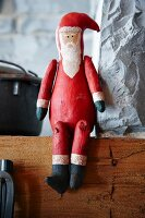 Wooden Father Christmas sitting on mantelpiece