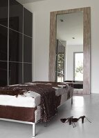 Chic dressing room with dark, glossy sliding doors on wardrobe, gigantic mirror and couch with animal-skin cover