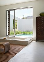 Modern, exotic luxury bathroom - sunken bathtub in front of open sliding terrace door with view of pool in courtyard