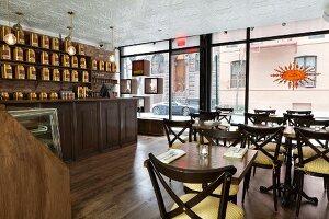Innenraum vom Bosie Tea Cafe mit großer Glasfront und goldenen Teedosen auf langem Wandregal über der Theke (Manhattan, New York)
