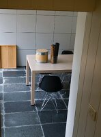 View through open doorway of table and black shell chairs on grey stone floor