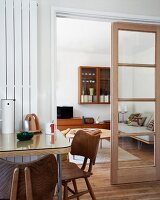 Dining area next to half-open wood and glass door with view of 50s-style living room
