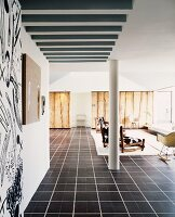 Modern, open-plan living space with column and armchairs on dark tiled floor