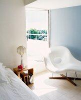 White chaise longue in front of terrace door in bedroom