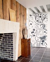 Brick fireplace on wood-clad wall opposite wall with black and white patterned wallpaper