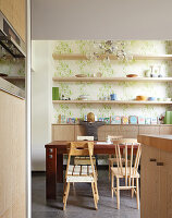 Kitchen with dining area in front of a wall niche with open shelving