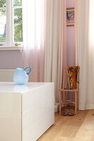 White half high drawer cabinet in a room and pink and white curtains at the window