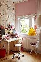 A desk and a wheeled chair in a child's bedroom