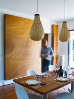 Man setting table in modern dining room with bulbous pendant lamps made from wooden strips