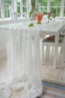 White, translucent fabric on dining table in loggia