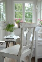 White kitchen chair next to bench and rustic side table in loggia
