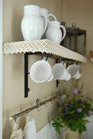 White china jugs and mugs on wall bracket with lace border