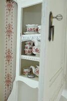 White kitchen dresser with open door showing traditional tea set with red and white floral pattern