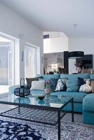 A blue corner sofa with decorative cushions and a metal and glass coffee table in a modern room