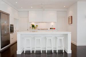 Designer kitchen with white island and retro bar stools