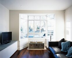 Living room with mixture of styles - modern leather sofa combined with seating on trunk in bay window