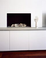 Modern fireplace with pebbles in hearth and sculpture on bench