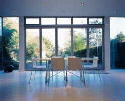 Minimalist dining area with light steel and wood furniture on tiled floor in front of large glass wall