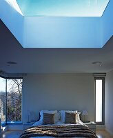 Double bed in modern bedroom with light from all sides