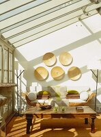 Conservatory with neo-classical sofa, antique wooden table and glass roof