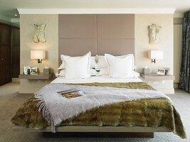Fur bedspread on double bed in modern bedroom