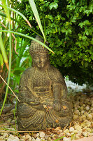 Oriental art- small, stone Buddha figurine on gravel