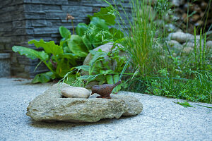 Stones and metal bird figurine on stone-flagged terrace