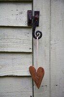 Heart hanging on latch of wooden door