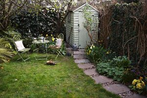 Garden table with two chairs next to shed