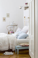 View through open bedroom door of comfortable country house bed and antique metal washstand with basin in background