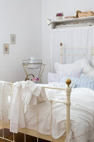Shabby chic bedroom - vintage metal bed with romantic bed linen and antique washstand in background