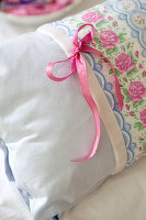 Romantic pink and pale blue pillow with pattern of roses and bow
