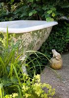 Stone frog next to old bathtub in garden