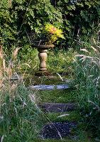 Basket of flowers on plinth in garden