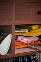 Colourful plastic handbags in open pigeonhole of shelves with mahogany veneer