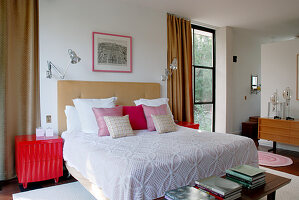 Scatter cushions arranged on double bed between two floor-to-ceiling windows with floor-length curtains in classic, modern bedroom