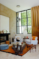 Modern living room with upholstered armchairs and various stools in front of fireplace and studio window