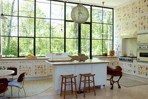 Kitchen in profusion of botanical motifs - free-standing island in front of cupboard doors covered in floral patterns and garden view through enormous windows