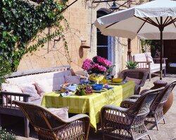 Rattan armchairs at summery set garden table
