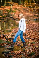 Woman crossing a stream in autumnal forest