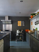 Grey kitchen counter and island in front of stainless steel cooker with extractor hood against grey-painted wall