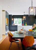 Kitchen-dining room: stained wood dining table, marble kitchen island and transparent lanterns