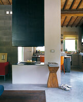 Open-plan interior in shades of green and blue below roof structure with terracotta tiles; open fireplace in centre