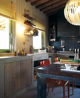 Rustic kitchen counter in blue-tiled kitchen with green-framed windows; blue vintage dining table in foreground