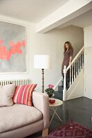 Lady going down stairs in a renovated country home with contrasting contemporary and antique furnishing
