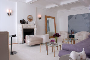Elegant, feminine living room in white and mauve with gilt-framed mirror and small glass tables with brass frames