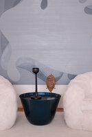 Plantpot-shaped side table between two faux fur armchairs with modern painting in background