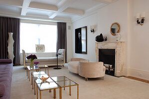 Elegant period living room with small brass and glass tables and unusual upholstered seating